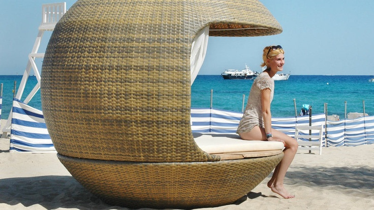 Cocoon Beach   by Cocoon Tree   Forget the sun umbrella—this orb-shaped beach shelter provides the ultimate in seaside shade and comfort. The aluminum structure is covered with straw-colored synthetic wire and has two foam mattresses and two sets of curtains—one tulle, the other of blackout fabric—for semi or complete privacy.                                    $8,000