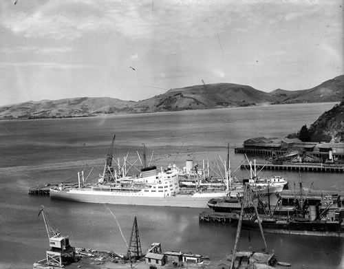 Port Chalmers, Dunedin in the 1950s – a traditional port scene with ships lying alongside narrow finger wharves. The most prominent vessel is the Port Auckland, constucted in 1949.