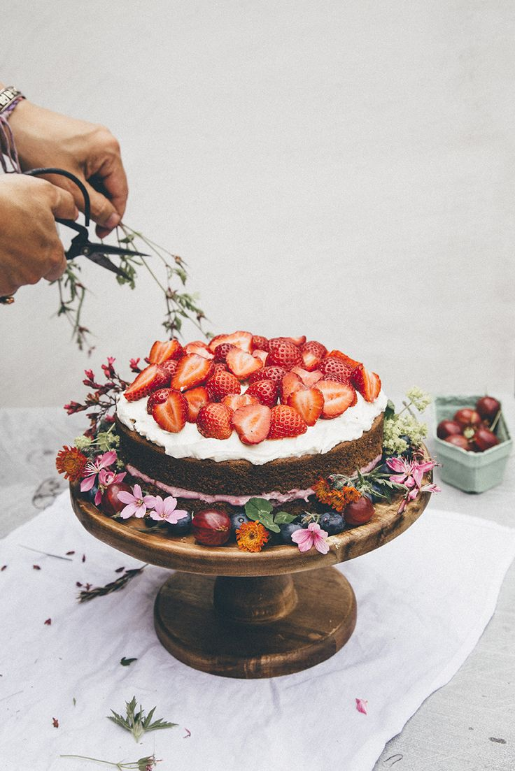 naked berry cake with white frosting on top + strawberries with floral + berry trim around the bottom
