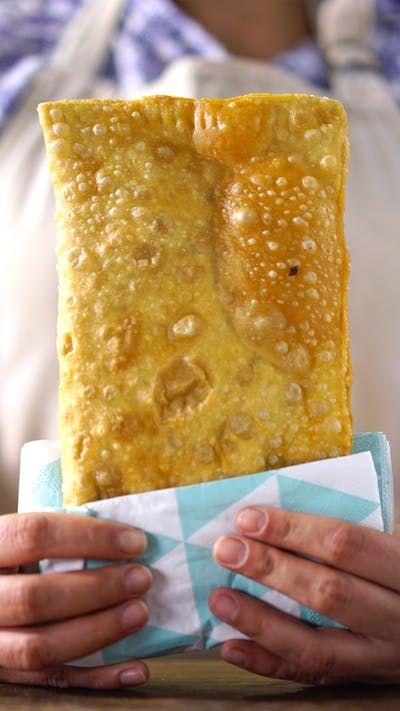 Receita com instruções em vídeo: O clássico pastel de feira crocante e sequinho na sua casa! Ingredientes: Azeite de oliva para refogar, 1 cebola picada, 2 dentes de alho picados, 500g de carne bovina moída, Sal a gosto, Pimenta do reino a gosto, ½ maço de salsinha picada, 7 xícaras de farinha de trigo , 1 pitada de sal, 400ml de água, 2 colheres de sopa de óleo, 1 dose de cachaça, 3 ovos cozidos, Óleo para fritar