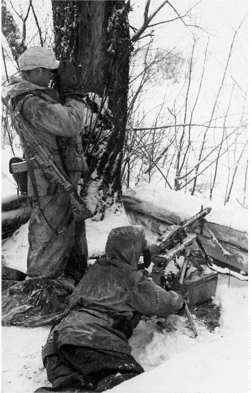 German soldiers in winter camouflage and heavy armed with a STG-44 and MG-42.  1944.