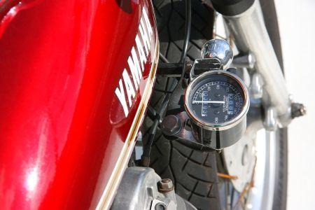 取材協力:山口輪業  コンパクトな車体が シングルエンジンの軽快さを増幅!!  新進気鋭の注目ショップ、山口輪業による1台がここに紹介するマシンだ。 余計な外装を取り外し、フューエルタンクにDT125純正を流用。シートはM&M'S製を加工。さらにフロントフォークは5cmローダウンで、リアサスペンションは280mmのローダウンサスを採用することで、まるで125ccを思わせるサイズ感を実現している。 他にもトラッカーハンドルをショート化することで、絶妙なライディングポジションとシルエットを作り出し、ヘッドライトに採用したトラクターフォグはマシンにビンテージ感をもたらしている。 しかし、そんな外観に反してFCRとスーパートラップの組み合わせは、スポーティな走りを予想させる。 ライトな仕上がりながらも、ビルダーのセンスによって上手くまとめられたビンテージトラッカー。だが、定番とはひと味もふた味も違う1台である。   ヘッドライトはトラクターフォグを採用。適度な径と厚みがマシンにビンテージ感をもたらせている。  フューエルタンクはDT125純正を流用加工。車種が違...