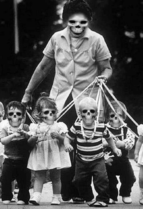 Daily Outing with the Damnlings of Connecticut. B & W Photo of a Nanny 'Herding' Children with Skull Faces on Leashes. Glorious Americana.