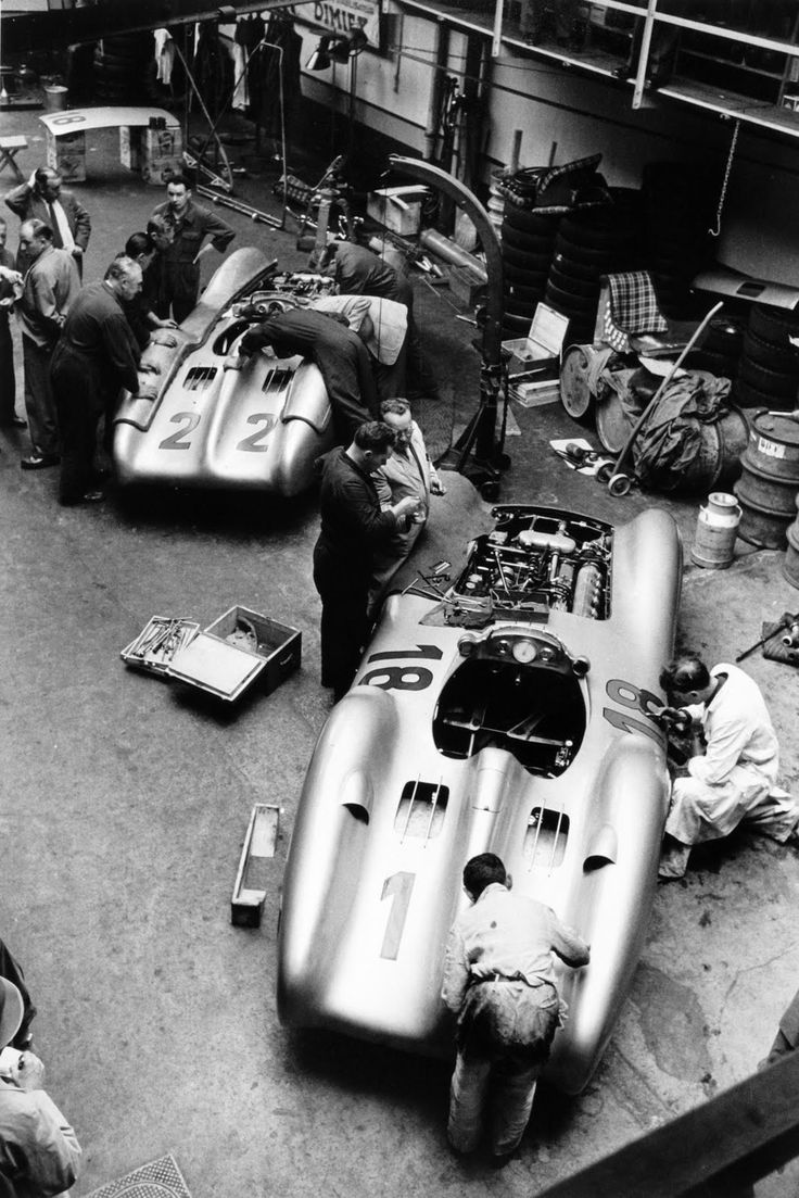 French Grand Prix. Reims, France. 4 July 1954. The cars of Hans Herrmann, Mercedes-Benz W196 #22, retired, and Juan Manuel Fangio, Mercedes-Benz W196 #18, 1st position, being worked on in the paddock, garage.  http://www.romeoauto.it