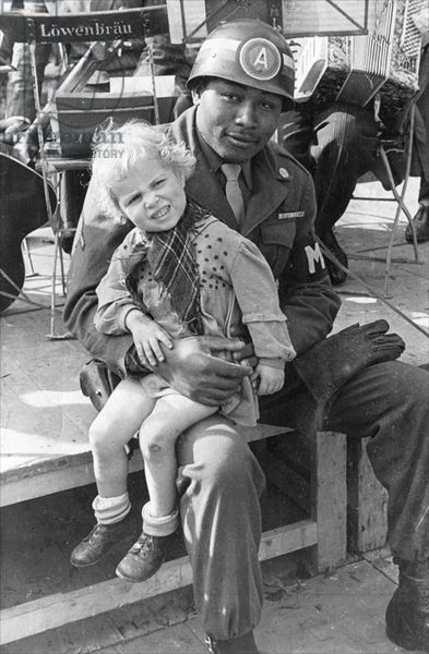 African-American soldier with a German child on his knee, Munich, 1945, (b/w photo)