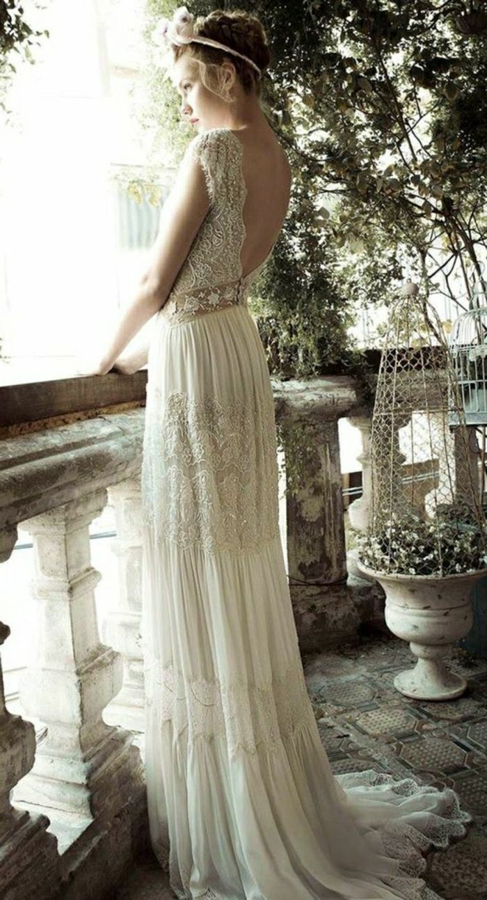 young blonde bride in vintage lace wedding gown with open back, with white hair ornament, standing on an antique looking balcony with trees and plants in the background