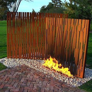 Laser cut corten steel behind fire