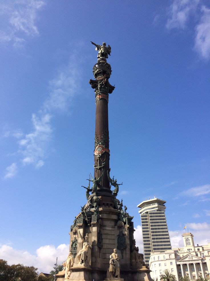 This is the Columbus Monument. It was created by  Rafael Atché in 1888 in honor of Columbus' first voyage to the Americas. It is 60 m tall and it is located at the lower end of Las Ramblas. In the statue, Christopher Columbus is holding a navigational chart in his left hand, and pointing to the route to America with his right. The monument serves as a reminder that Barcelona is where Christopher Columbus reported to Queen Isabella and Ferdinand after his trip.