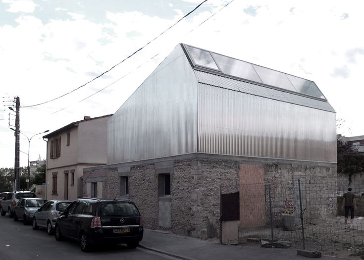 House renovation by BAST contrasts old brick base with metal extension