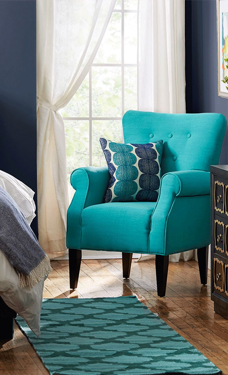 Showcasing rolled arms and tapered wood legs, this charming tufted arm chair  brings a pop