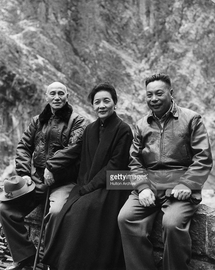 Chinese leader Chiang Kai-Shek (left) sitting on a stone wall with Madame Chiang Kai-Shek (1897 - 2003) and their son, Lieutenant General Chiang Ching-Kuo.