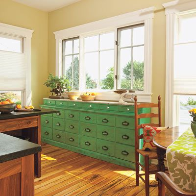 A painted pharmacy cabinet under a trio of kitchen windows adds a spot of color to this vintage kitchen. | Photo: Deborah Whitlaw Llewellyn | thisoldhouse.com