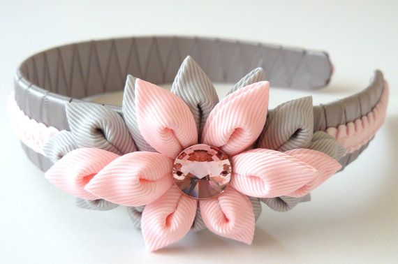 A flower is made in the technique of tsumami kanzashi.  Plastic headband is weaved with satin ribbon.  Flowers are made from grosgrain ribbons. Swarovski