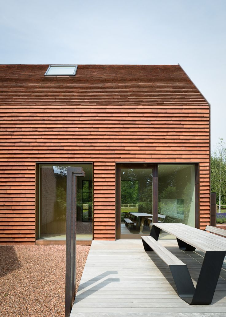 Terracotta hued tile, copper...very interesting exterior material palette. Family home in Olmen by Pascal Francois