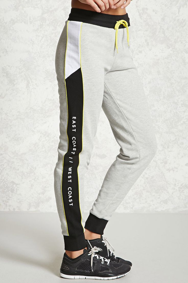 "A pair of knit athletic joggers featuring ""East Coast West Coast"" graphics on the sides, colorblock panels, contrast piping, French terry cloth lining, a drawstring waist, and cuffed ankles."