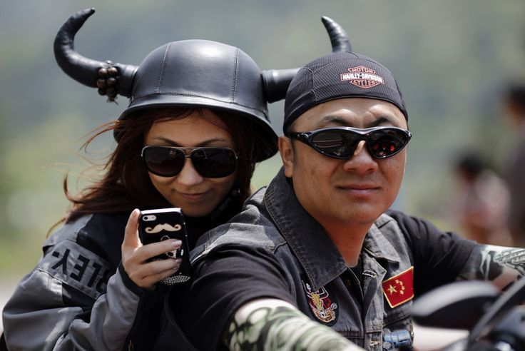 A couple rides a Harley Davidson motorcycle during the annual Harley Davidson National Rally in Qian Dao Lake, in Zhejiang Province, China, on May 11, 2013. (Credit: Carlos Barria/Reuters)