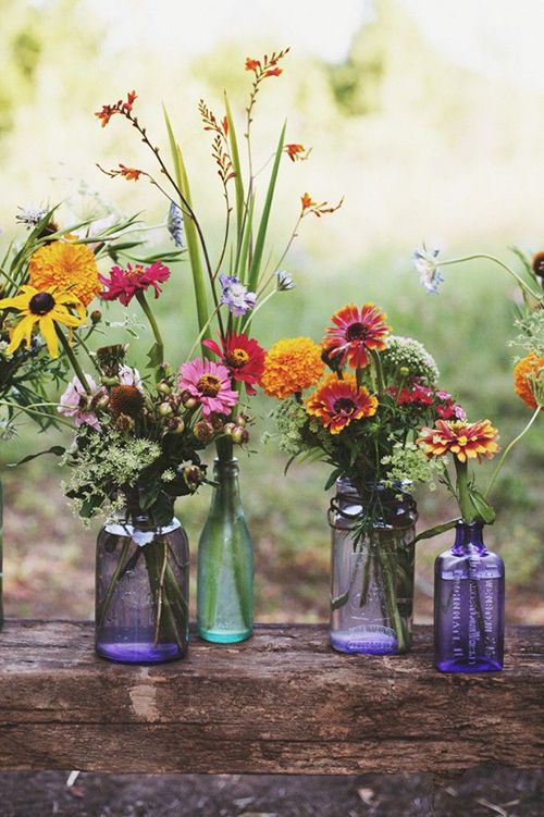For a rustic, hand-picked feel, arrange wildflowers and textured grasses in purple and green bottles | Brides.com