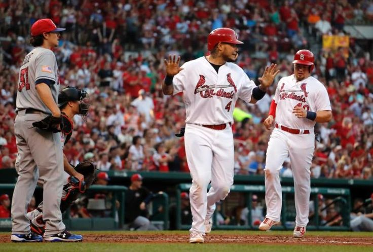 St. Louis Cardinals' Yadier Molina (4) celebrates after scoring with teammate Luke Voit, right, as Miami Marlins starting pitcher Jeff Locke, left, stands by during the third inning of a baseball game Monday, July 3, 2017, in St. Louis. (AP Photo/Jeff Roberson)