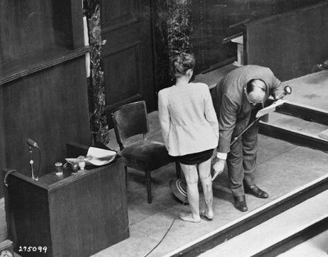 Concentration camp survivor Jadwiga Dzido shows her scarred leg to the Nuremberg court, while an expert medical witness explains the nature of the procedures inflicted on her in the Ravensbrück concentration camp on November 22, 1942. The experiments, including injections of highly potent bacteria, were performed by defendants Herta Oberheuser and Fritz Ernst Fischer. December 20, 1946.  — National Archives and Records Administration, College Park, Md.: Scarred Leg, Medical Experiments, Expert Medical, Witness Explains, Nuremberg Court, Medical Witness, Concentration Camps