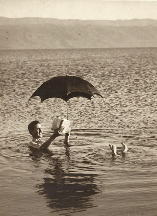 Swimmer Reads a Book Holding an Umbrella over his head while he floats in the Dead Sea, Israel ca. 1920. Photo by Buyenlarge / Getty Images. °