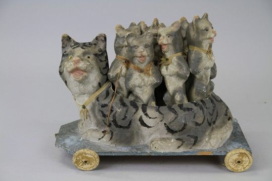 CAT SKITTLES SET  Germany, very nice visual display detail to mother cat holding nine kittens, in standing pose, used as skittles, each paper made piece colored in grey overall with silk neck piece, wheeled platform.