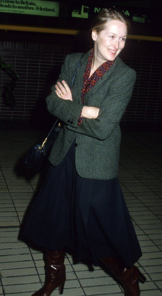 Streep wore a collegiate blazer, midi skirt, and leather boots to Heathrow airport in 1980.