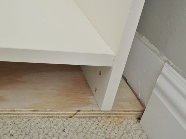Raising the bookcase with a plywood base gives support on the carpet and makes it the right height for the baseboard trim