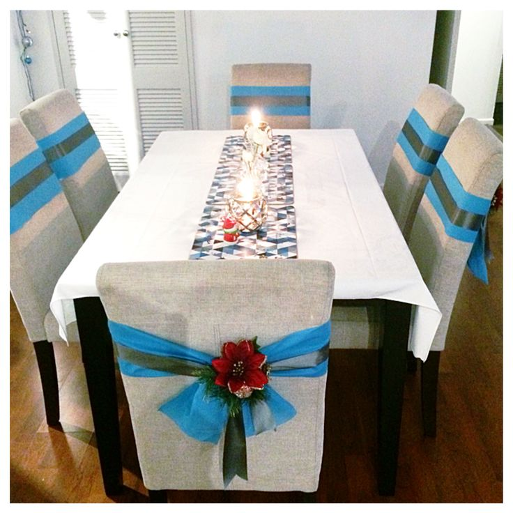 Christmas table decorated modern blue & red contemporary with a traditional feel. Chairs wrapped in ribbons