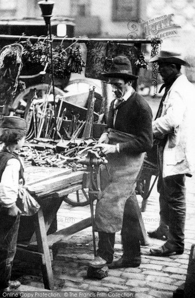 London, The Knife Sharpener, Whitechapel Road 1885. This cutler and locksmith has an establised stall in the market in the Whitechapel Road. He is a general jobber, able to sharpen knives and tools, re-set saws, repair locks and cut replacement keys. Hanging on the rail behind are huge clumps of keys. #London #HistoricLondon