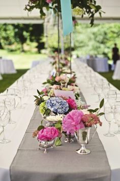 Melbourne Cup event styling - silver trophies as centrepieces with bright spring flowers