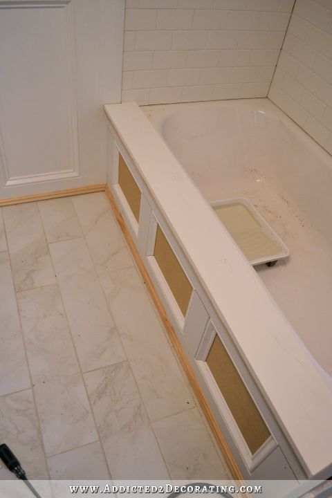DIY bathtub skirt - step 7 - add a ledge to the top using silicone adhesive #DIYAtticRemodel