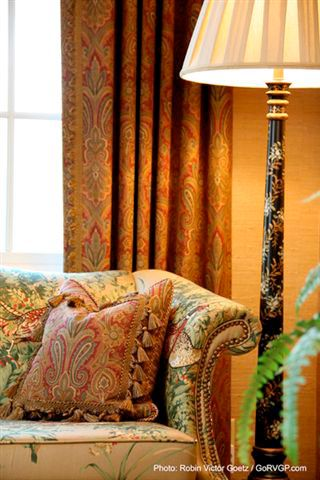 Living room with burnt orange walls and paisley curtains