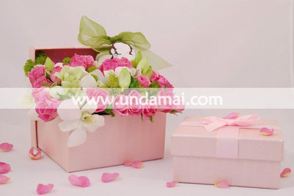 Aranjament floral pentru 1-8 martie realizat sub forma unei cutii cadou cu miniroze roz si orhidee alba Dendrobium; accesorizata cu camee si funda organza