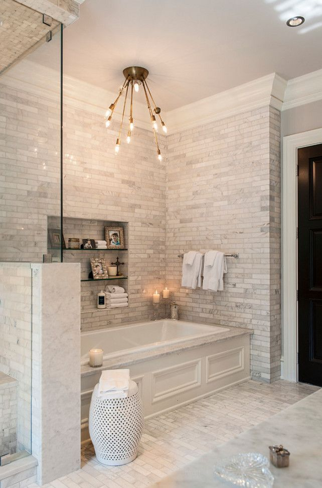 Best reading spot in the house!  Bathtub with modern light fixture, grey brick walls, and built-in glass shelves: