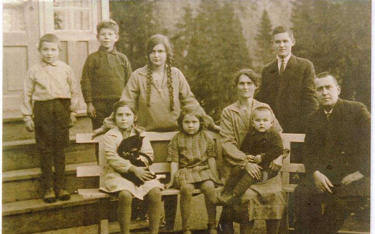 Another old picture of my grandmother, the girl holding the cat, and her family.
