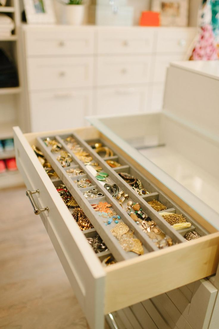 Custom drawers organize jewelry and accessories in this walk-in closet with miles of style. Built for Cooking Channel star Tiffani Thiessen, the modern space has a neutral backdrop that turns Thiessen's clothing and shoes into the room's focal point.