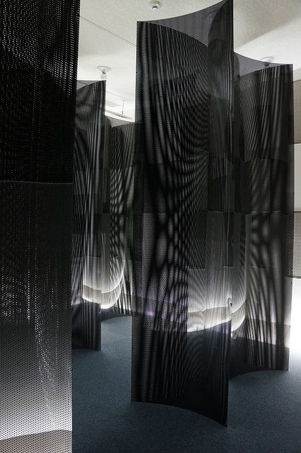 White Dots Columns by oxoxo [zero by zero], via Flickr | Seven triangular prisms with punched plastic boards are installed in the room. If you walk around the room, the patterns change dynamically