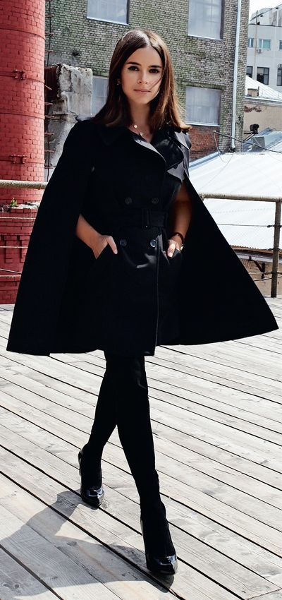 Miroslava Duma wearing an all-black outfit with black cape, photographer unknown