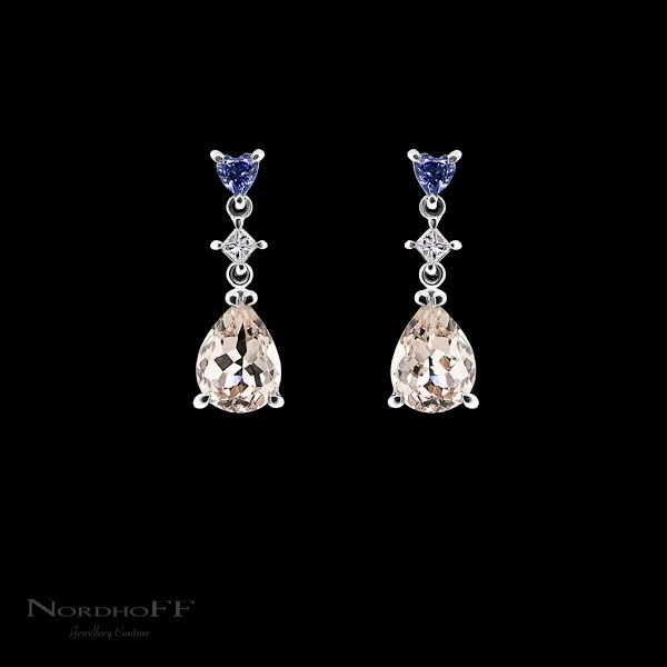 Bright blue heart shaped sapphires sit at the top of these handmade articulated earrings and contrast beautifully with the soft pastel tones of the pear cut morganites. Between the two sits a bright princess cut diamond adding a touch of sparkle. The perfect bridal earrings to incorporate your something blue.