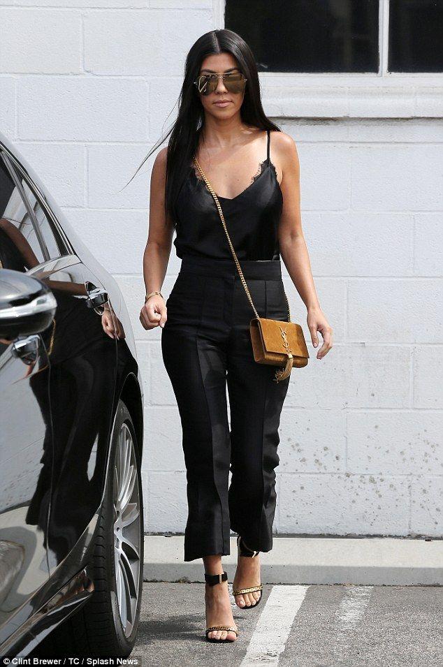 Fashion touchdown! Kourtney Kardashian channeled her sexy side as she sported a black silk...