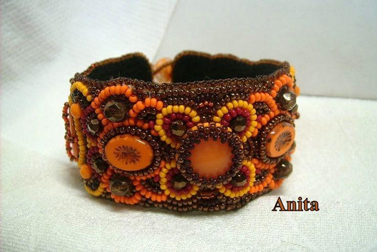 K-711. Narancs és barna színű, gyöngy-hímzéssel készített széles karkötő. Kapcsolója gyöngyből van. Ára: 3700.-Ft.
