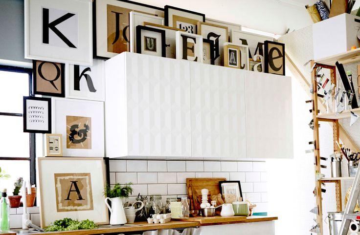 Rahmen mit Bilderdrucken in Schwarz, Weiß und Beige rund um einen weißen Küchenschrank drapiert.