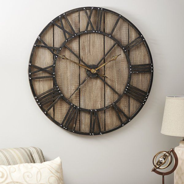 This Roman Numerals Vintage Wall Clock makes telling time easier on the eyes. The clock's backing is made to look like aged barnwood. It has black metal framing and large Roman Numerals on its dial cut from the same black painted metal. Silver studs dot the frame wherever the numerals join it for a striking, yet simple, accent. The hands of the clock are metal too, telling the time with a minute and hour hand. This stunning Roman Numerals Vintage Wall Clock really strikes a chord for home…