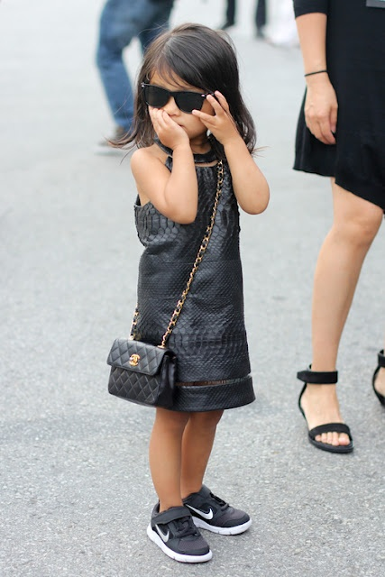 Little girl is on point, leather dress, sun glasses and the whole attitude to match.