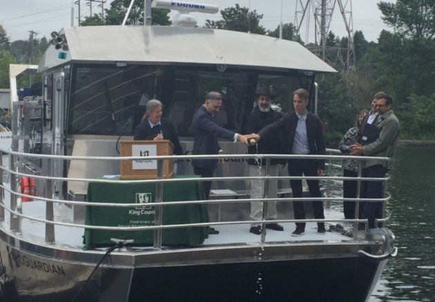Matt Cameron and Kim Thayil of the band Soundgarden pour champagne off the bow of the SoundGuardian research vessel with King County Executive Dow Constantin...