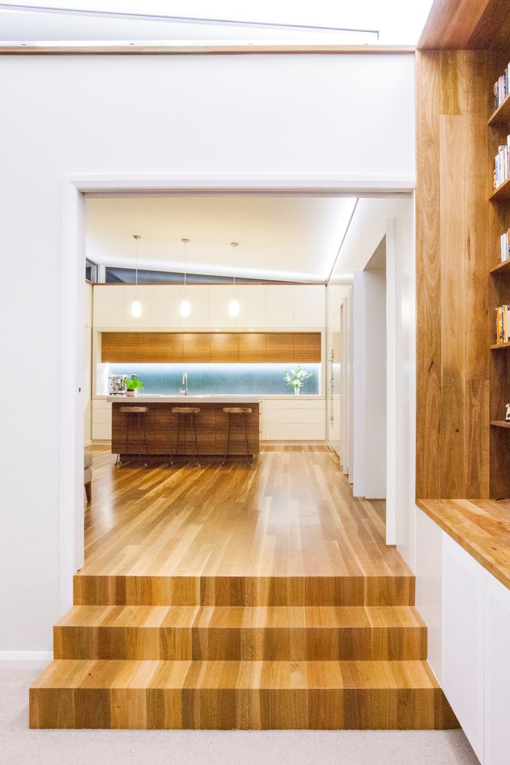 Steele Associates carpentry team took great pride in mitring and matching the Spotted Gum flooring to line the steps from kitchen to living room, creating a cascading effect as the floor plane folds over the stairs.