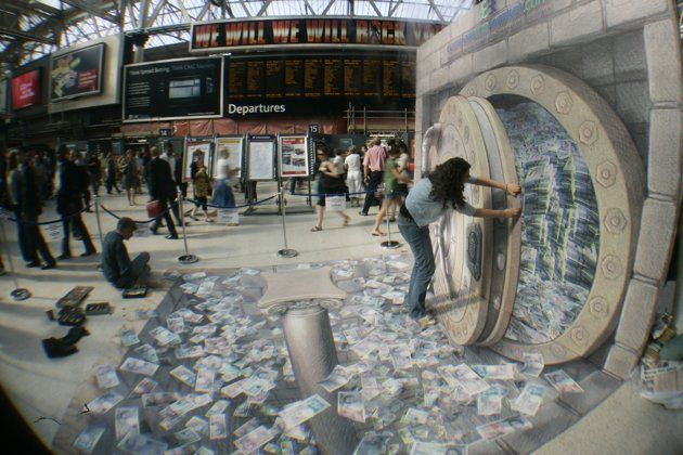 A woman poses in U.S. street artist Kurt Wenner's 3D illustration of an open vault containing British currency, fluttering out at Waterloo station, London, July 24, 2008.