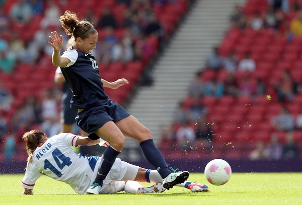 Lauren Cheney of USA is tackled by Louisa Necib of France during the Womens Football first round Group G Match of the London 2012 Olympic Games between United States and France, at Hampden Park on July 25, 2012 in Glasgow, Scotland.