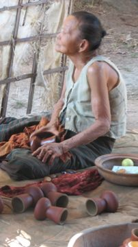An elder Thai woman, burnishing pots for 3 bhat a day.  (about $1), 2007