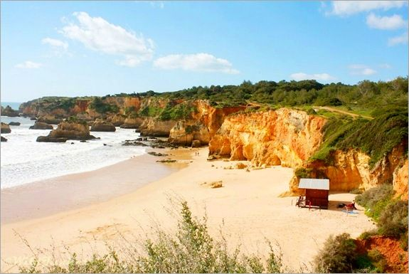 Photoblog: The Rocky Cliffs of Algarve, Portugal - by Nellie Huang, Wild Junket Magazine | Surfers get ready to ride the waves while holidaymakers lounge under the shade of the cliffs to soak in the languid undercurrent. | Photo: Algarves cliffs at Portimao beach. Portugal